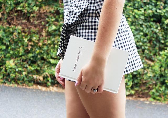 venku na cestě je žena s krátkými kostičkovanými šaty, jdou jí vidět stehna a drží zápisník, fotka pouze na pas
