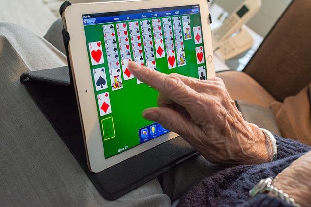 ruka seniorky hrající na tabletu